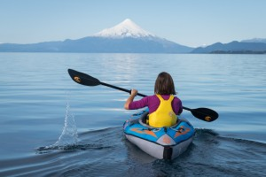 A lady on a kayak on a lake with a snow capped volcano in the background enjoying the best time to visit Chile