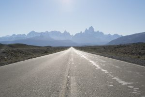 A grey road with the Fitzroy mountain range in the back. El Chalten, Argentina