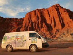 A sunset photo of a condor campervan against some glowing red rocks in talampaya, argentina